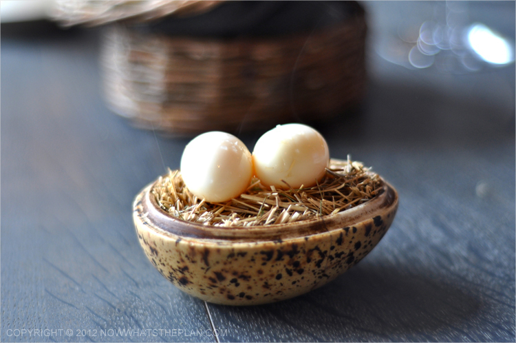 Two quail eggs served on top of a egg-shaped saucer filled with hay