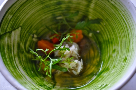 Crab meat and egg yolk in broth topped with herbs in a beautiful brushed bowl