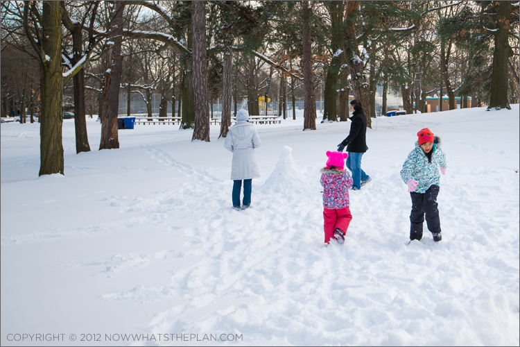 Family making a snowman in High Park Toronto