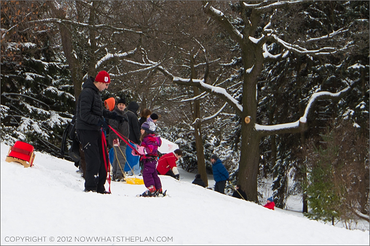Dad helping daughter with ski shoes in High Park Toronto